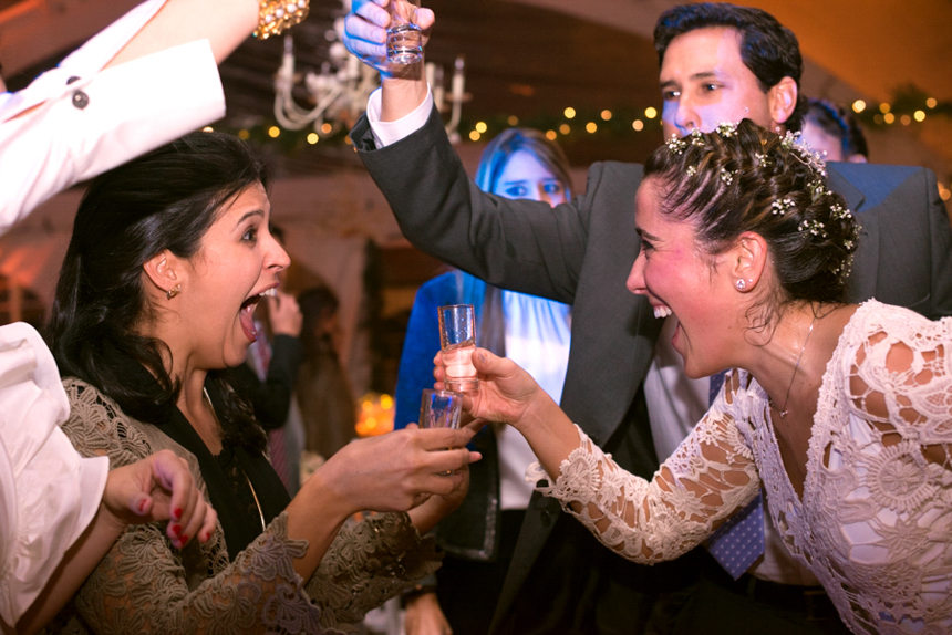 bride-and-wedding-guests-taking-shots-wearing-lace-dress