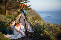 tropical-bohemian-wedding-captured-in-Big-Sur-lovers-cozy-up-in-a-teepee-bride-wearing-a-aimple-long-sleeve-wedding-dress