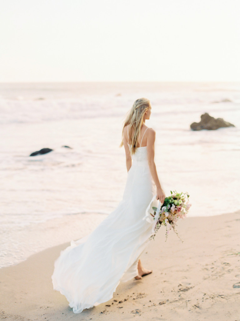 bohemian-bride-walking-through-the-sand-with-flowers-in-her-hair-wearing-a-simple-boho-wedding-dress