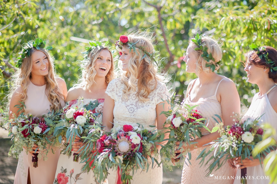 bohemian-bridesmaids-wearing-mismatched-dresses-while-bride-wears-open-back-lace-gown