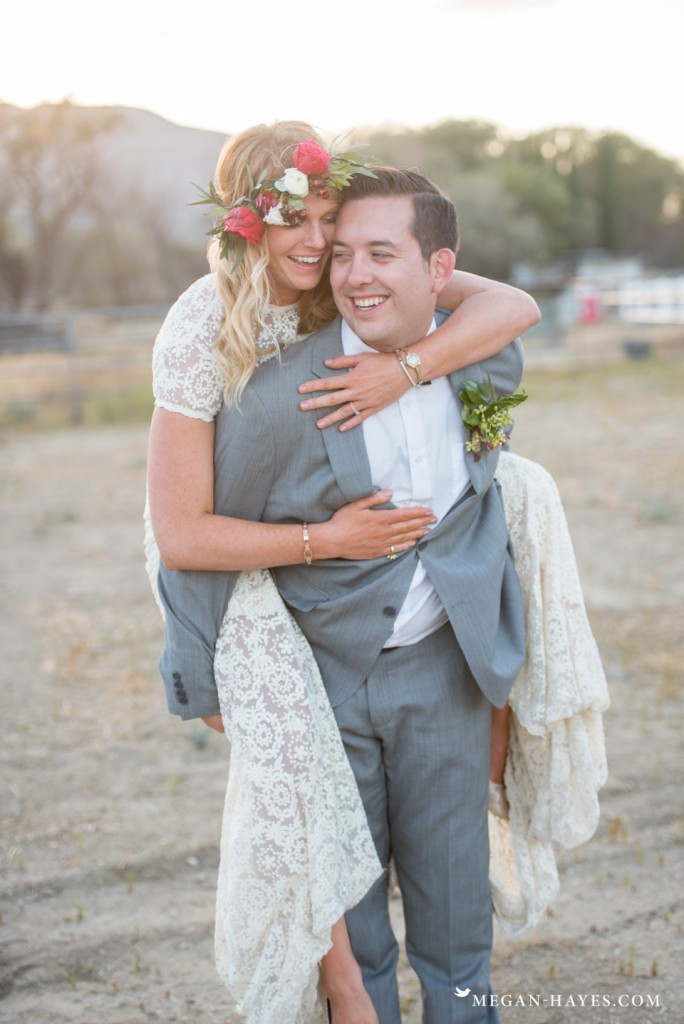 a-bride-piggyback-rides-her-husband-while-wearing-her-backless-lace-bohemian-wedding-dress-a-testament-to-its-comfort