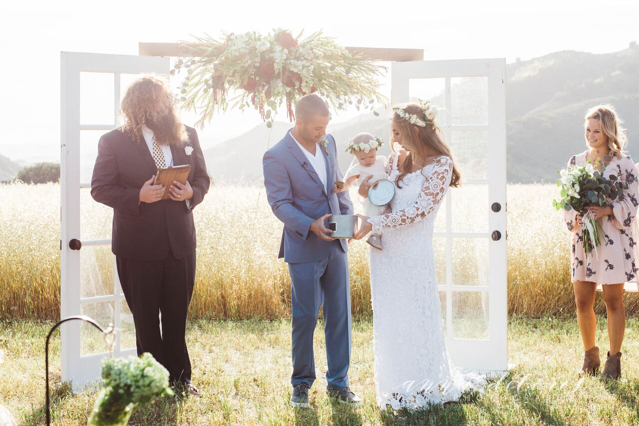 gorgeous-bride-and-groom-with-their-baby-at-the-altar-at-figueroa-mountain-farmhouse-wedding-in-california