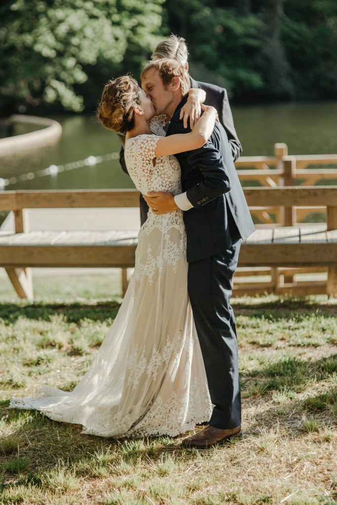 bohemian-couple-steal-a-kiss-at-their-laidback-camp-wedding-ceremony--she-wears-the-azalea-handmade-lace-wedding-dress