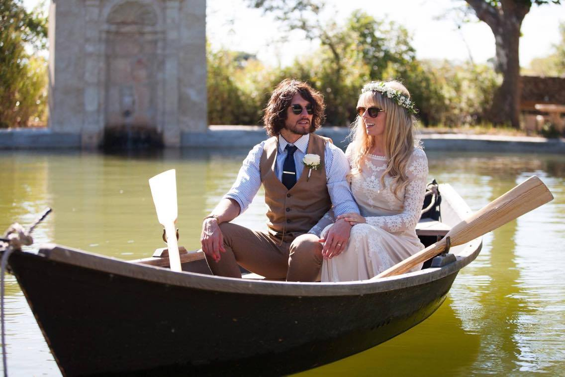 bride-and-groom-in-row-boat-in-the-south-of-France-her-in-a-boho-lace-wedding-dress-wearing-raybans