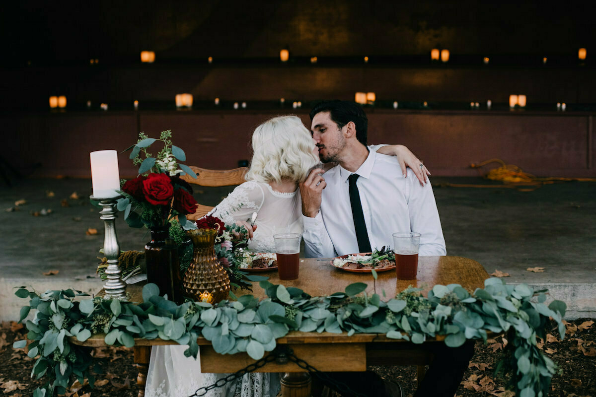 bride-and-groom-surrounded-by-greenery-and-flowers-at-the-sweetheart-table-bohemian-wedding-inspiration