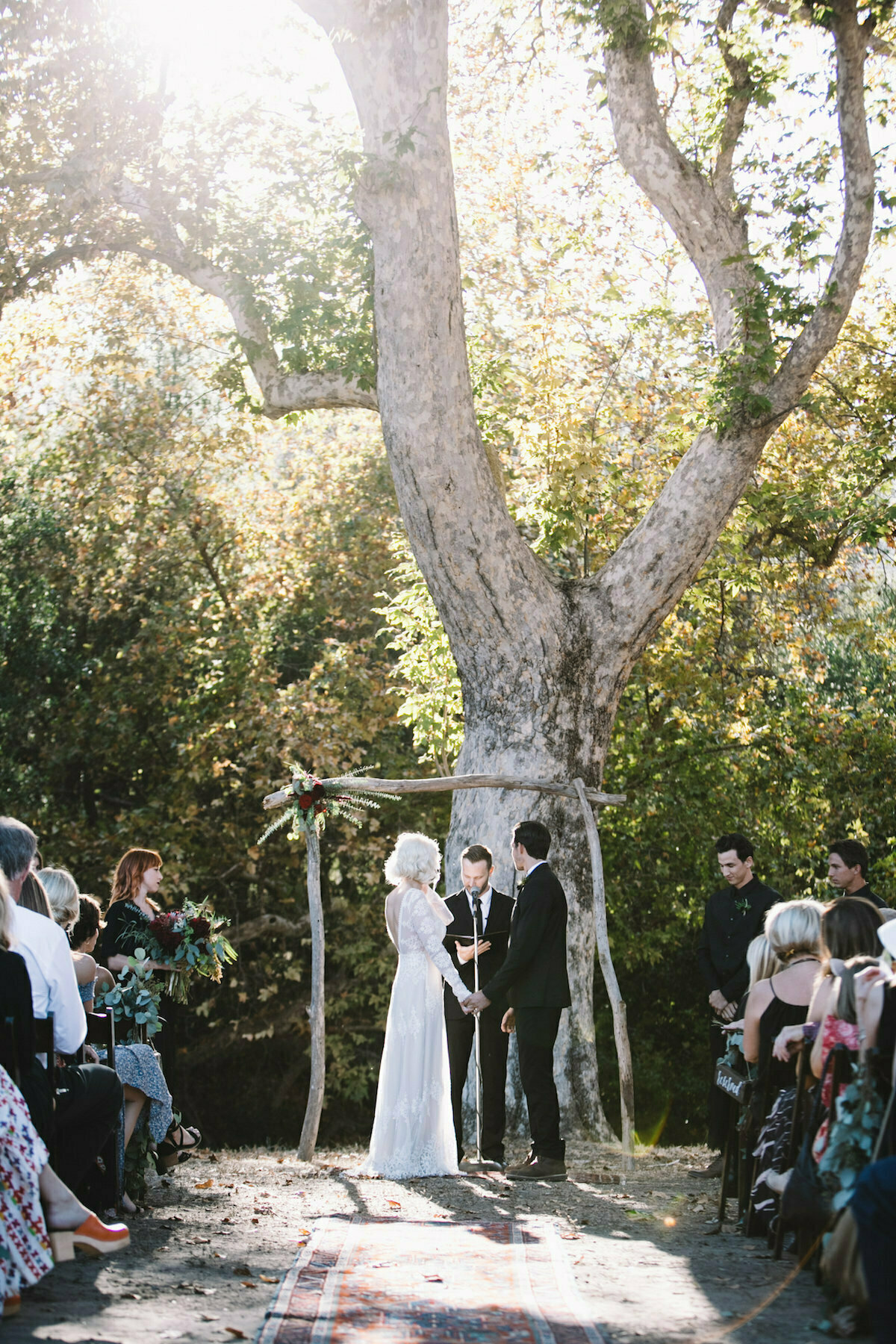 bride-wearing-lisa-backless-dress-with-her-husband-under-a-tree-arched-altar-saying-their-I-dos