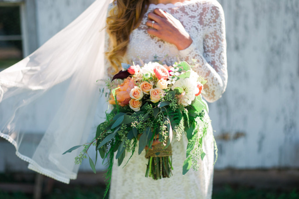 a-Virginia-lakeside-bohemian-wedding-bride-here-wearing-long-sleeve-simple-lace-wedding-dress-with-a-beautiful-peachy-flower-bouquet-boho-wedding-inspiration