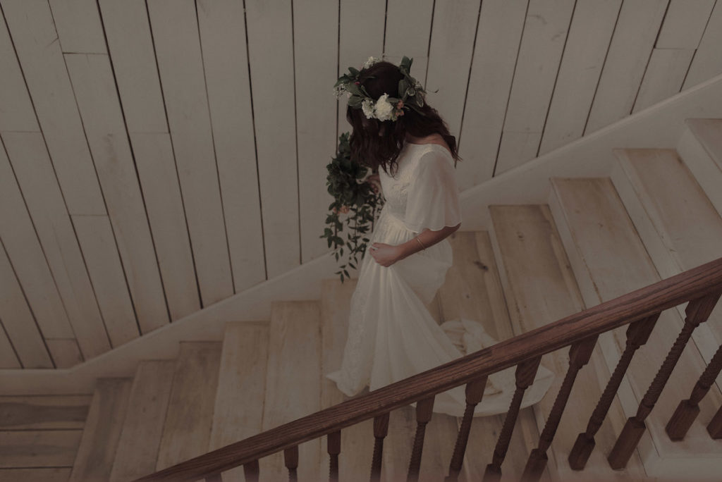 bride-saran-walking-down-the-stair-wearing-a-flower-crown-and-her-boho-wedding-dress
