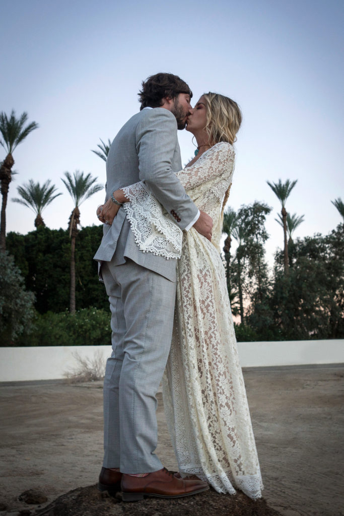 bohemain-loving-bride-wearing-a-lace-caftan-finished-with-a-fishtail-raid-and-flowers-in-her-hair-at-her-palm-springs-wedding