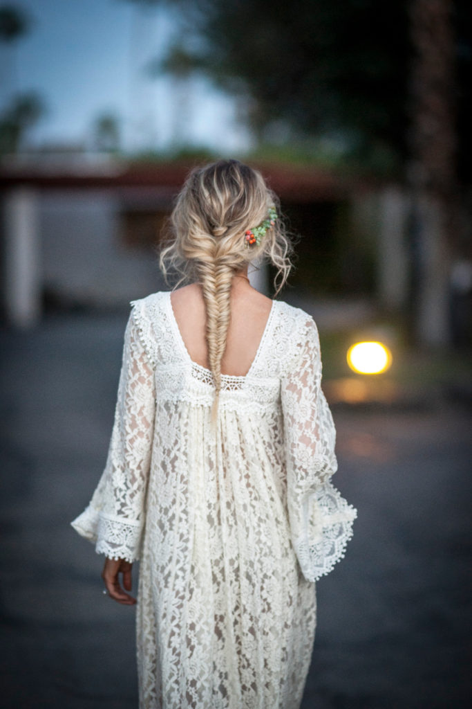 a-boho-bride-wearing-a-lace-caftan-with-a-gorgeous-fishtail-braid-and-flowers-in-her-hair