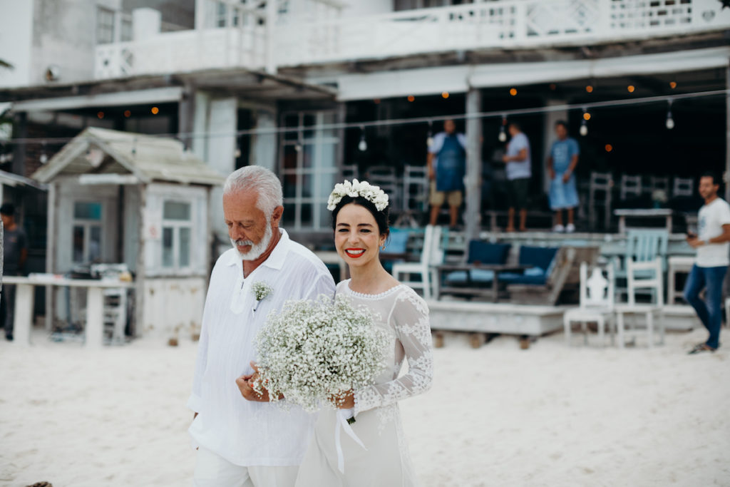 the-smile-on-bride-Carolina's-face-as-she-walks-with-her-dad-carrying-a-baby's breath-bouqet