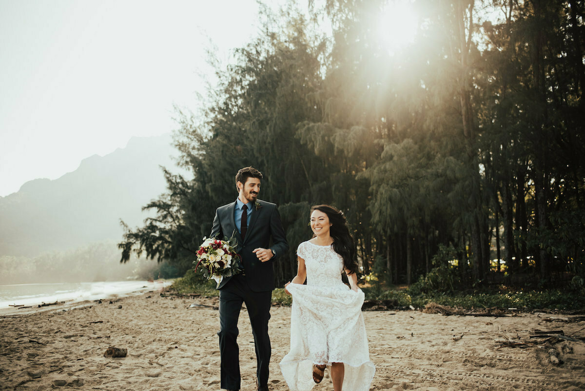 a-happy-bride-wearing-a-simple-bohemian-white-lace-dress-with-her-groom-hawaii-boho-beach-weddings