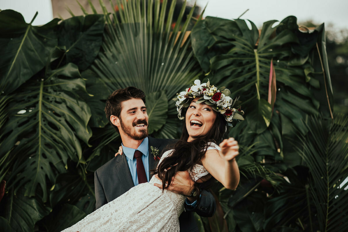 happy-bride-being-carried-by-her-new-husband-she-wears-a-tropical-flower-crown-and-a-simpe-lace-dress