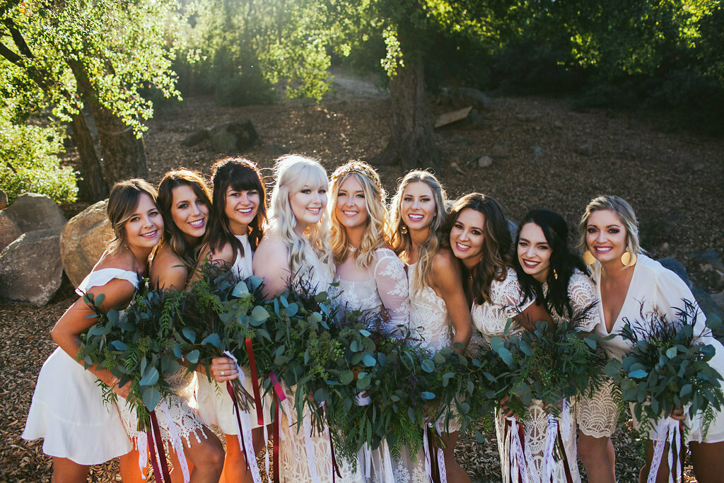 bridesmaids-with-greenery-bouquet-and-mismatched-white-dresses-boho-wedding-inspiration