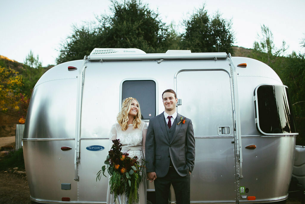 bride-and-groom-standing-in-front-of-a-vintage-airstream