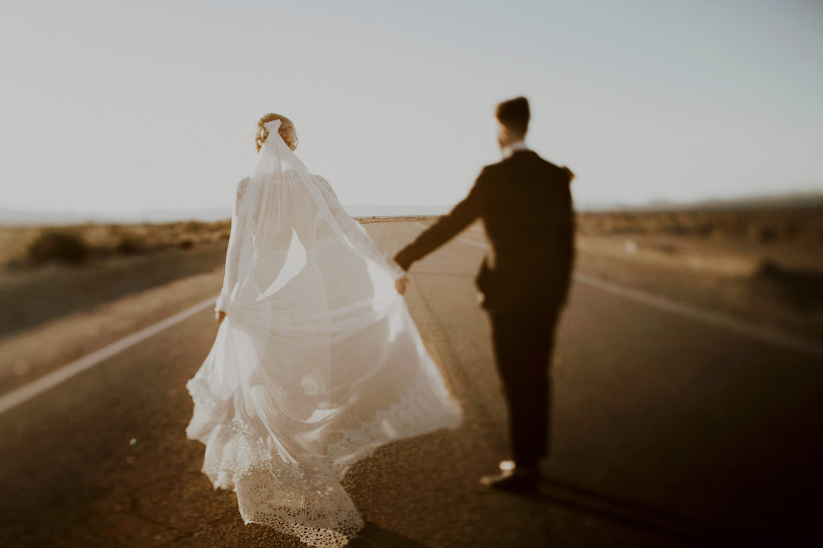 bride-julia-wearing-lace-dress-and-long-veil-at-their-palm-springs-boho-wedding