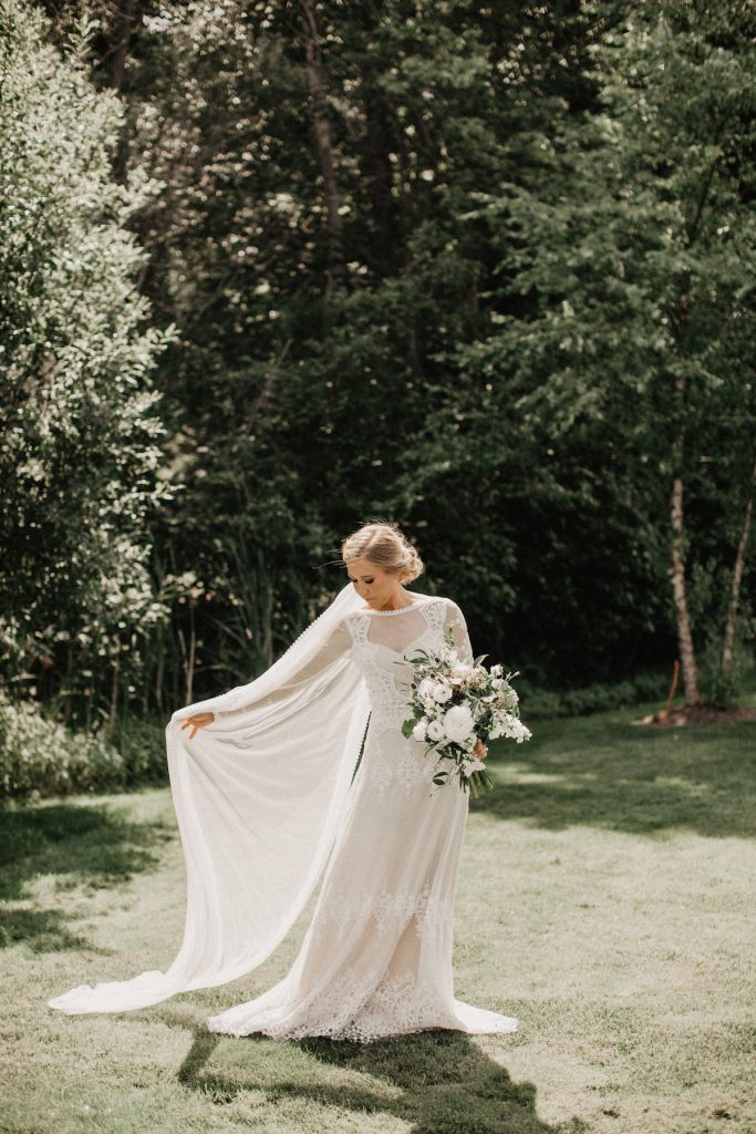 bohemian-bride-wearing-dreamy-simple-long-veil-with-a-subtle-green-white-bouquet-in-a-whimsical-lace-flowy-wedding-dress-with-nature-as-the-perfect-backdrop