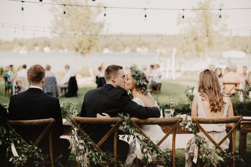 bride-sitting-at-lakefront-michigan-bohemian-wedding-filled-with-greenery