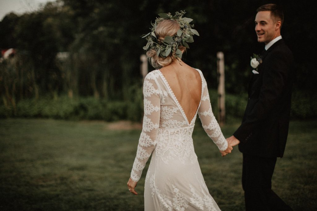 walking-hand-in-hand-her-in-a-romantic-flowy-wedding-dress-with-small-train