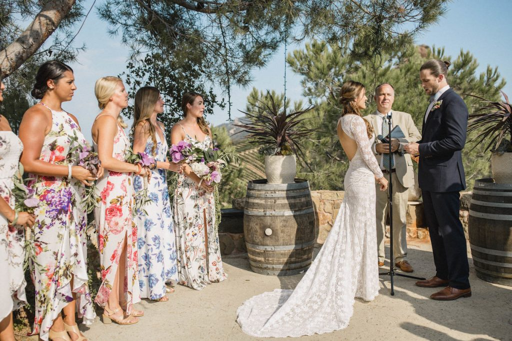 magical-ceremony-at-saddlerock-ranch-bridesmaids-wears-floral-dresses-bride-wearing-a-long-sleeve-backless-lace-wedding-gown