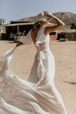 Feel-free-in-the-Hayley-lace-and-crepe-romantic-wedding-dress-with-cape-sleeves-flowy-skirt-with-sash-belted-waist