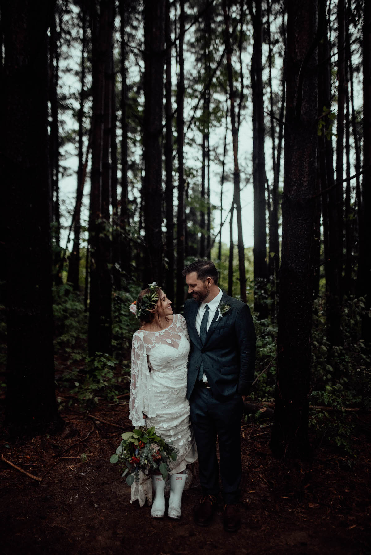 Bride wearing rain boots with her lace wedding dress